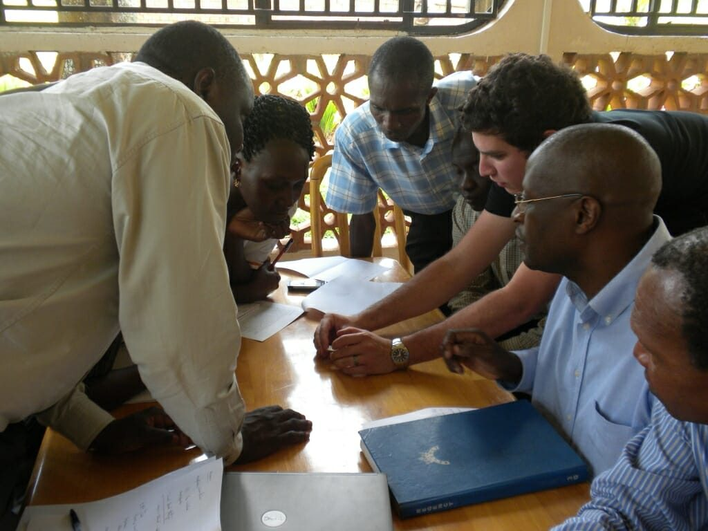 Photo of researchers from Salus Discovery training Uganda-based staff on a diagnostic test for HIV/AIDS